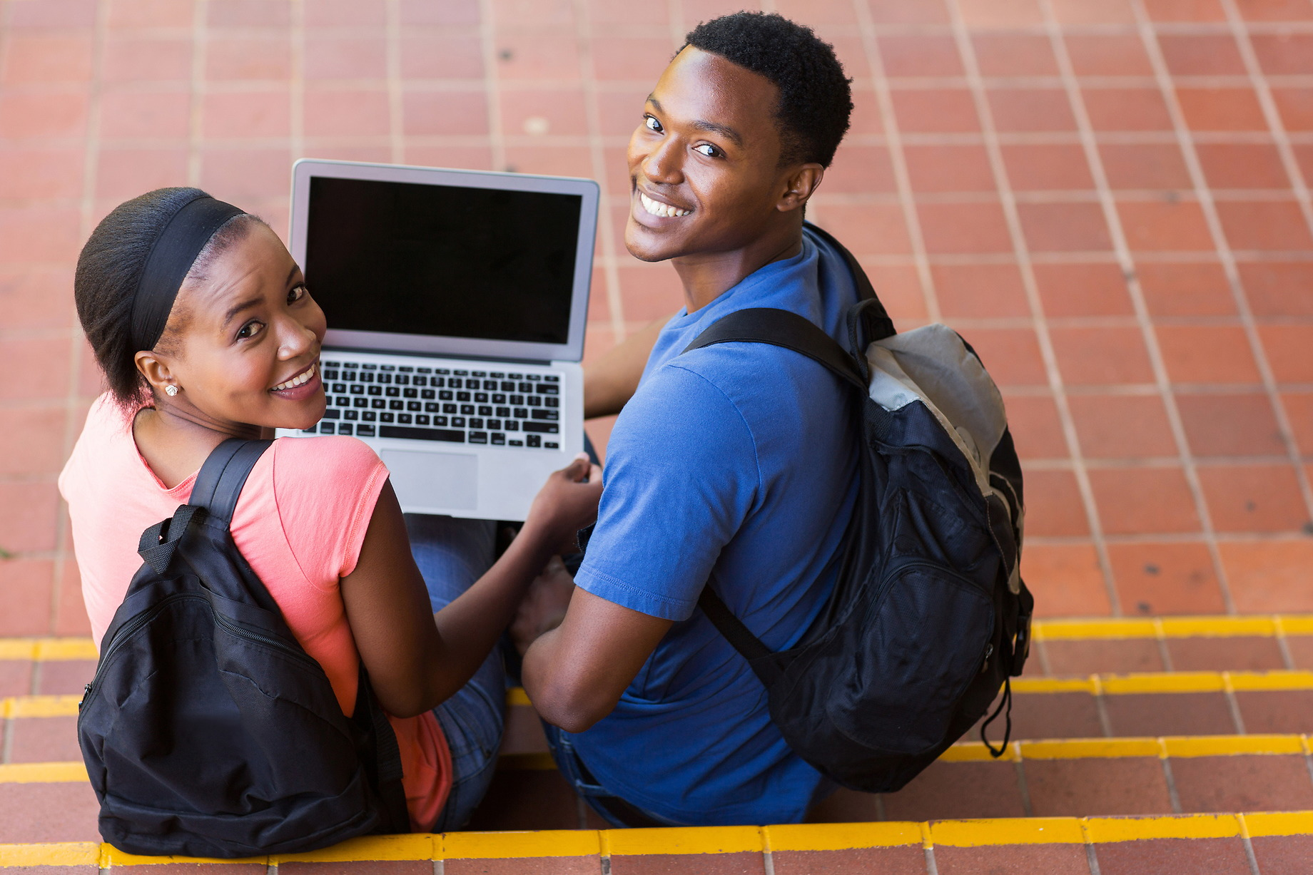 Two Students looking over their shoulders holding a laptop